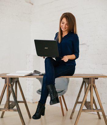 Žena sedící na pracovním stole.